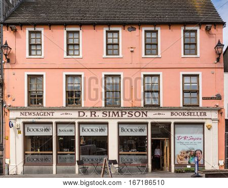 Wick Scotland - June 4 2012: Closeup of the pink painted storefront of Wick book store and coffee shop. Tables and chairs upfront. Three levels of windows. Street lanterns of facade.