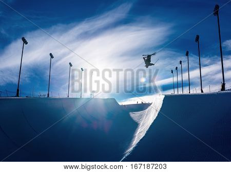 Skier doing an inverted trick in a winter snow halfpipe