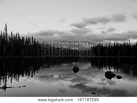 The sun sets over Scott Lake in Oregon's Cascade Mountains and lights up the clouds that reflect in the lake that is accented by boulders and the reflections of trees on a summer day.