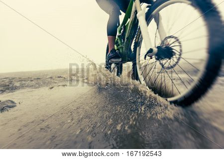 Low angle shot of a mountain Biker Racing Through Puddle