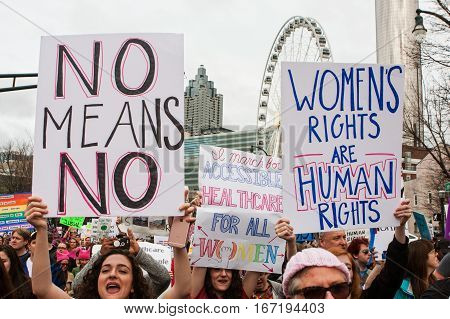 ATLANTA, GA - JANUARY 2017:  Women hold up signs in support of women's rights as thousands of protesters participate in the Atlanta march for social justice and women the day after President Trump's inauguration in Atlanta GA on January 21, 2017.