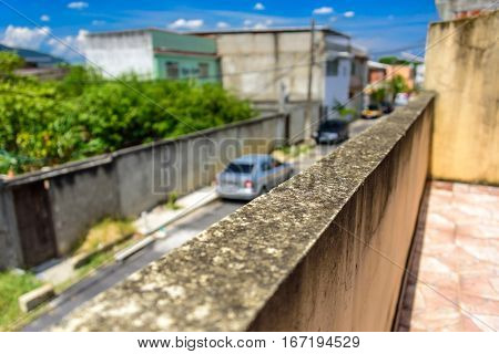 The moldy wall and blurry street with cars and houses in Bangu neighborhood, where the prison, the Penitentiary Complex of Gericino and Bangu dump are located, the West Zone of Rio de Janeiro, Brazil