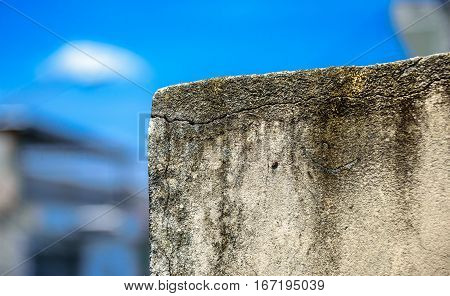 The moldy wall on the background of blurry buildings and bright blue sky at sunny summer day