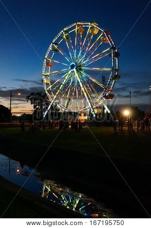 Gaily Lit Ferris Wheel Reflects in Water as Sun Sets