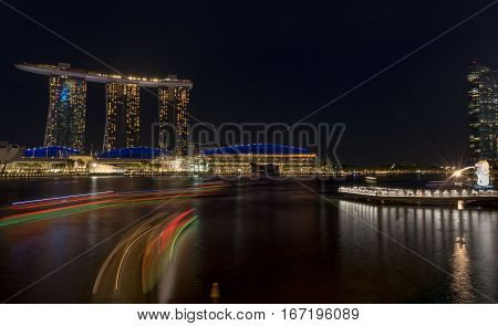 night time cityscape of Singapore with light reflections in the water - built on reclaimed land