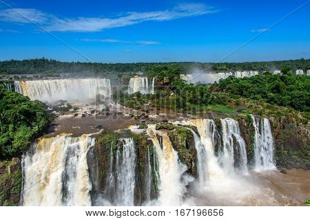 Aerial view of waterfalls cascade of Iguazu Falls with extensive tropical forest and powerful flows of water in Iguacu National Park, UNESCO World Heritage Site, Foz de Iguacu, Parana State, Brazil