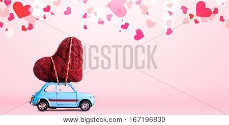 Blue retro toy car delivering craft heart for Valentine's day on pink background with confetti