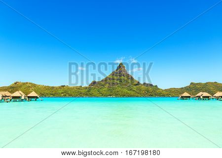 View on Mount Otemanu through turquoise lagoon and overwater bungalows on the tropical island Bora Bora Tahiti French Polynesia Pacific ocean.
