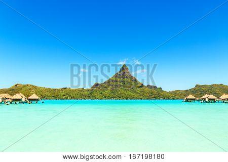 View on Mount Otemanu through turquoise lagoon and overwater bungalows on the tropical island Bora Bora Tahiti French Polynesia Pacific ocean.