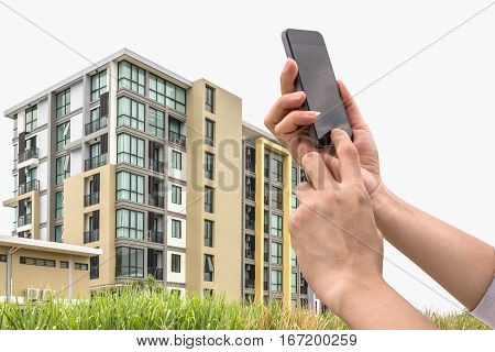 hand holding and touch screen smart phone looking for a new condominium in suburb.