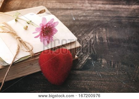 Red heart and vintage novel book - concept of love story nostalgia and remembrance in valentine's day. vintage color tone