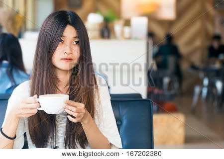 Asian Women Sitting In Library With Cup Of Coffee To Make A Idea For Start Up Business
