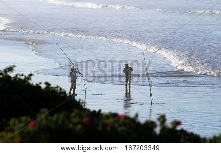 Two fishermen fishing at the beach, standing on wet sand with ocean in background.