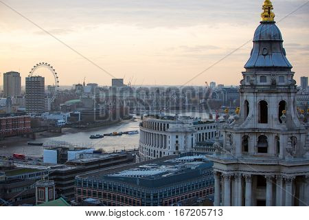 London, UK - December 19, 2016: London at sunset, view from the St. Paul's cathedral. Panoramic view includes London eye, river Thames and embankment