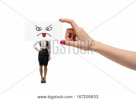Small businesswoman on while background and a giant hand covering her face with a piece of paper with a drawn sad face. Business and success. Corporate world. Occupational issues.