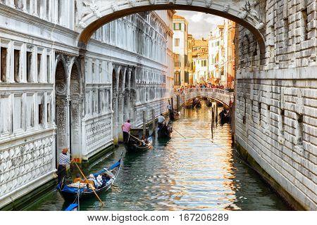 Tourists In Gondolas Sailing Under The Bridge Of Sighs In Venice