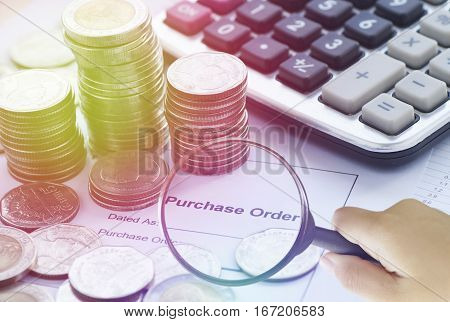 Magnifier finding purchase order with calculator and money coins concept in account and business