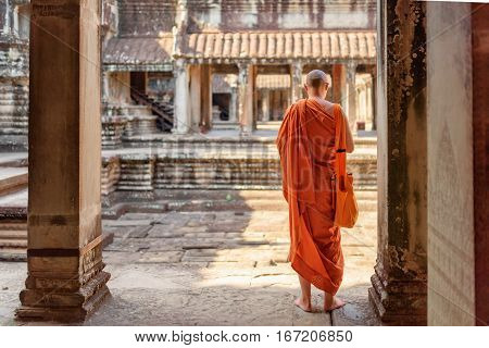 Buddhist monk exploring ancient courtyards of temple complex Angkor Wat in Siem Reap Cambodia. Amazing Angkor Wat is a popular destination of tourists and pilgrims.