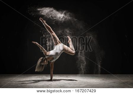 Slender girl dancing in cloud of white dust staying on one hand studio shot