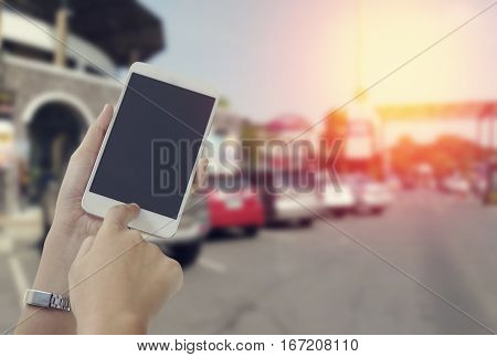 women's hand touch screen of phone with car backgroundconcept in asking for help and communication