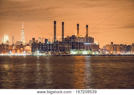 Power generation plant in New York City at night time on river bank.