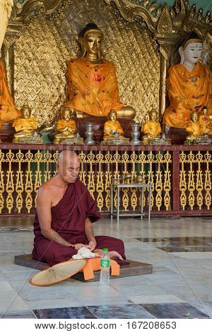 YANGON, MYANMAR - DECEMBER 17, 2016: A buddhist monk meditates in one of the temples of the Shwedagon pagoda