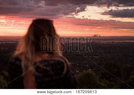 Girl photographing a red sunset over Perth city from the hills in Kalamunda. Western Australia, Australia.