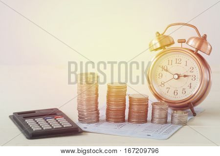 pile of money coins on book bank with clock calulator for business background