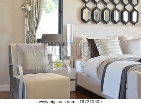 Modern Bedroom Interior With Gray Pillow On Armchair And Bedside Table Lamp At Home