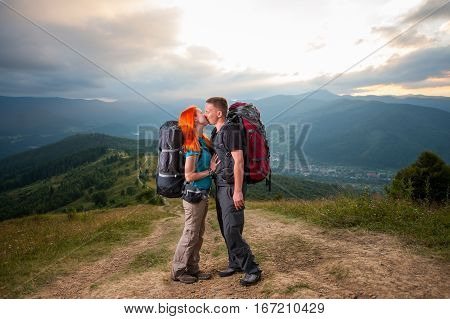 Man And Red-haired Woman On The Road In The Mountains