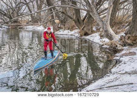 winter stand up paddling on the Poudre River in Fort Collins, northern Colorado - senior male paddler in a drysuit enjoying his workout