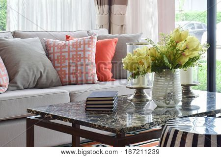 Books And Decorative Items On Marble Top Table And Lively Sofa Set