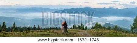 Couple Tourists Standing On A Hill Enjoying A Morning Haze