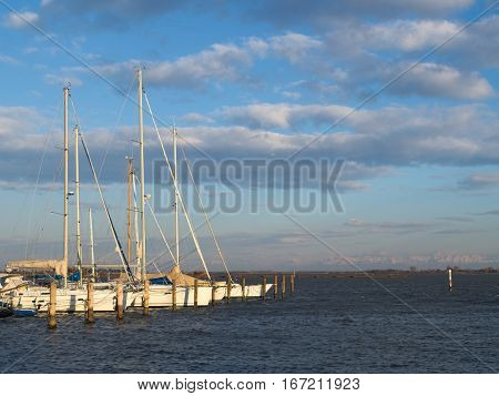 Some sailboats moored in the harbor of the town of Grado, Italy with the Alps mountains on the background