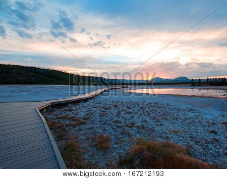 Sunset View Of Walkway Going By Turquoise Pool In The Midway Geyser Basin In Yellowstone National Pa