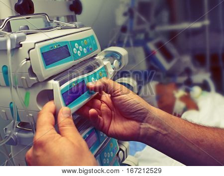 Medical worker configures equipment in tthe ICU.