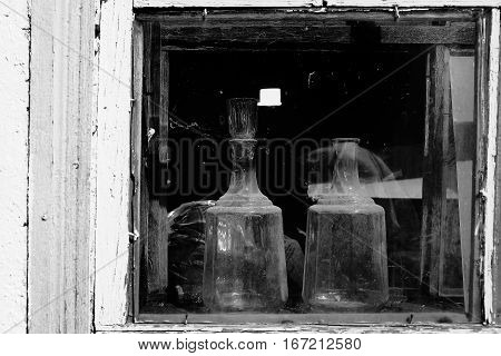 Two kitchen glassware in the window of an old village house.
