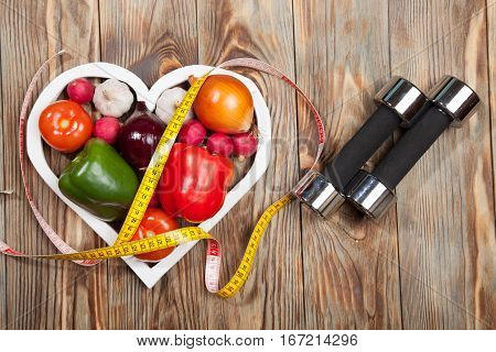 Sport and diet. Vegetables, dumbbells and centimeter. Peppers, tomatoes, garlic, onions, and radishes in the heart on rustic background