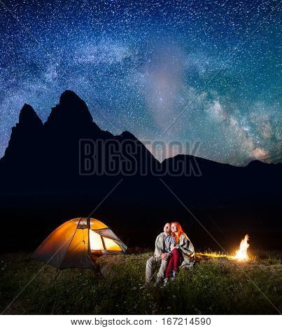 Two Lovers Tourists Sitting Together Near Campfire And Shining Tent At Night Under Stars And Looking