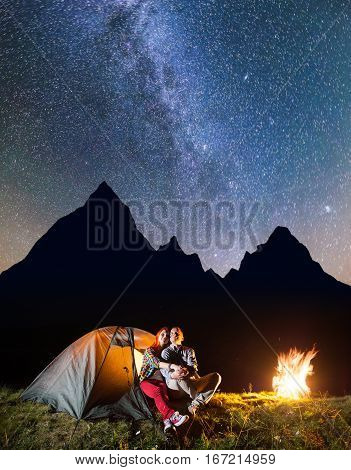 Couple Tourists Sitting Near Tent And Campfire, Looking To The Shines Starry Sky And Milky Way In Th