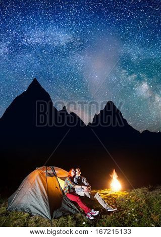 Romantic Couple Hikers Looking To The Shines Starry Sky And Milky Way In The Camping At Night Near C