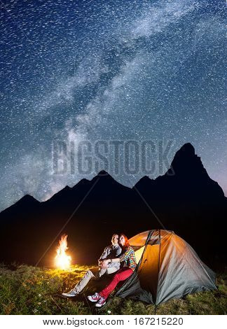Tourist Couple - Girl And Guy Looking To The Shines Starry Sky And Milky Way In The Camping At Night