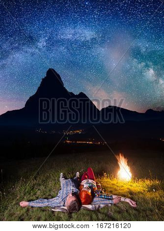 Happy Couple Hikers Admiring The Bright Stars And Lying Near The Fire At Night. Long Exposure