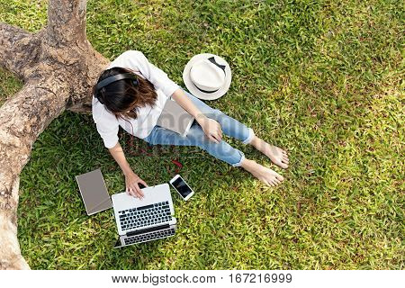 woman sitting at green grass using labtop