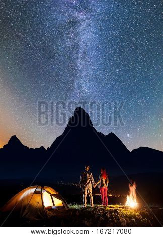 Night Camping. Romantic Hiker Couple - Girl And Guy Holding Hands, Standing Near Tent And Campfire,