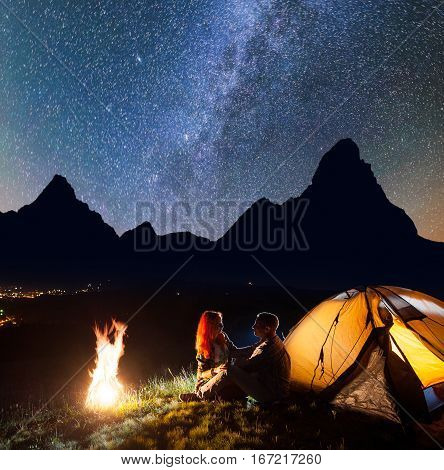 Night Camping. Charming Pair Tourists Sitting Face To Face In Front Tent Near Campfire Under Shines