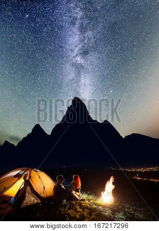 Romantic Couple Tourists Sitting Face To Face In Front Tent Near Bonfire Under Shines Starry Sky At