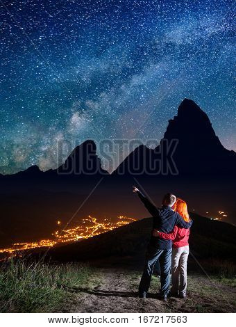 Man Hugging Red-haired Woman And Shows On Stars And Milky Way In Beautiful Starry Sky At Night. Astr