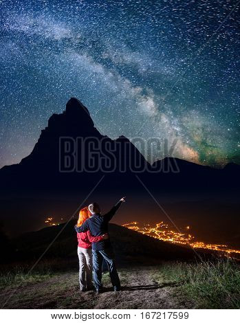 Guy Hugging Red-haired Girl And Shows On Stars And Milky Way In Beautiful Starry Sky At Night. Long
