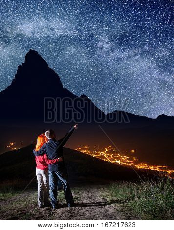 Tourist Family - Man And Woman Hugging. Male Hiker Showing On Stars And Milky Way In Beautiful Starr